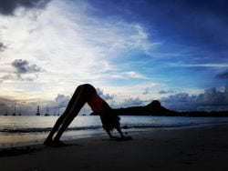 A picture of a girl doing yoga on the beach in St. Lucia at sunset